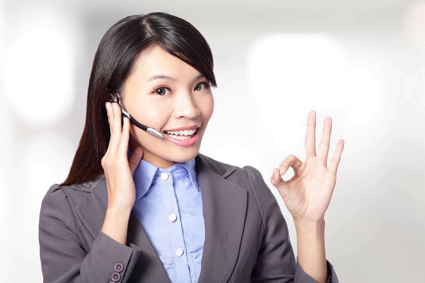 beautiful  customer  service  operator  woman with headset and smiling ,one hand touching the headset and the other hand show to ok sign, asian woman